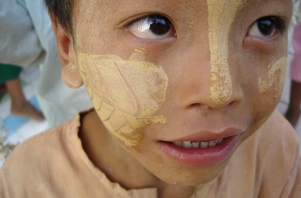 Child in Burma wearing traditional thanaka makeup